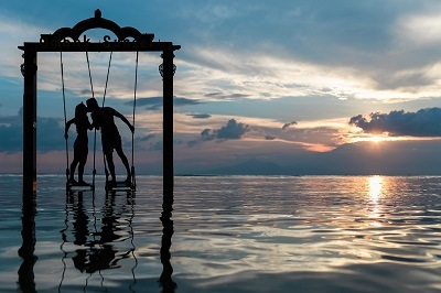young man and woman are kissing each other while holding a rope above the sea water