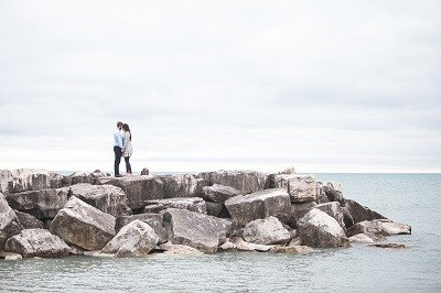 young man and woman holding hands standing on a rocky area next to ocean