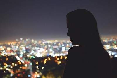 a sad looking girl after a breakup watching city night lights from the window of her apartment