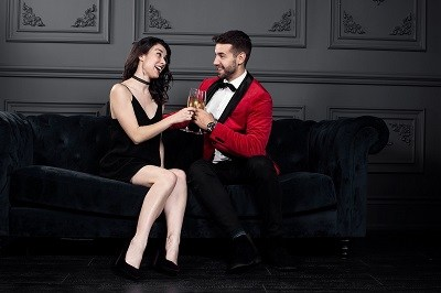 young man and woman sitting on a sofa at a party clinking glasses and having a good conversation