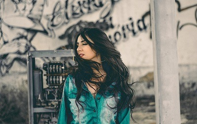 beautiful woman standing next to a pole while the wind blowing her thick hair away from her face