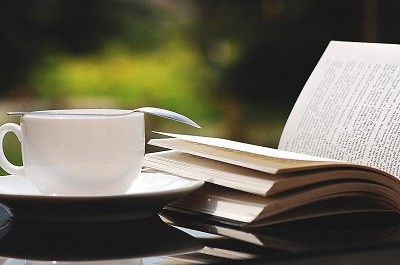 an open book on a small desk next to a coffee cup and spoon