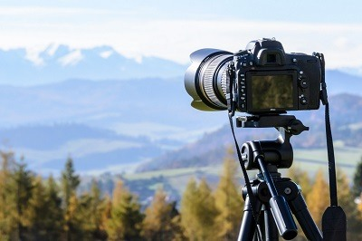 DSLR camera on tripod facing beautiful landscape