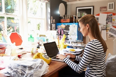 business woman writing email call to action using a laptop at her home office
