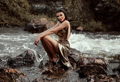 beautiful female fashion model sitting next to a river posing for fashion shot