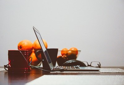 laptop on a desk next to a basket of fruits