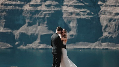 newly married couple hogging next to a lake