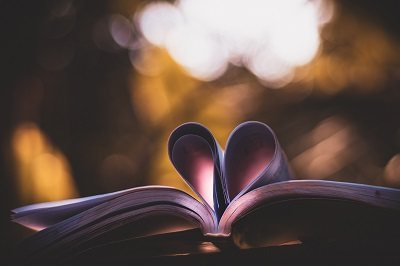 open book with pages curled to shape of a heart with bright light in the background