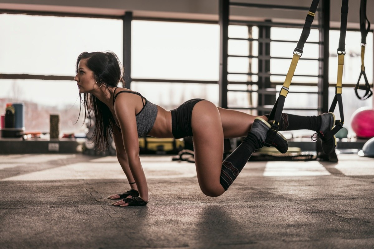 a beautiful woman displaying a unique exercise for the whole body with a simple home exercise equipment