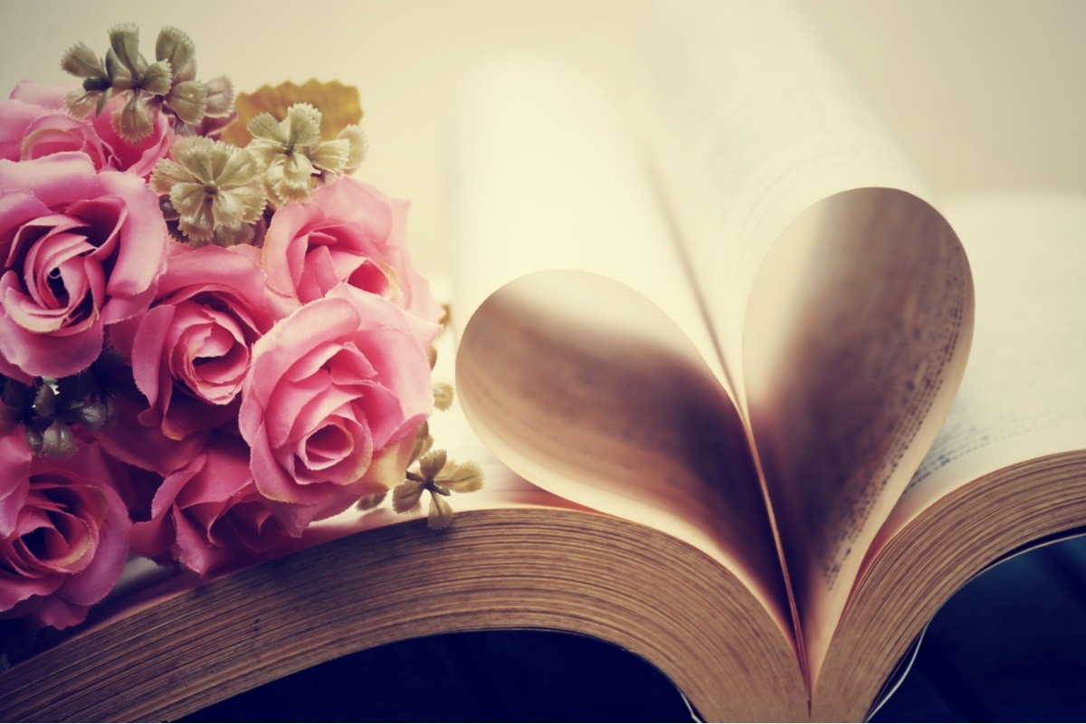 book with pages curled into a heart shape with pink rose flowers on top