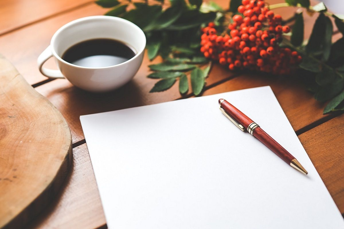 antique pen on top of a notepad next to a cup of coffee on a wooden table