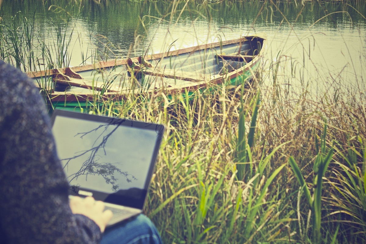 an entrepreneur is using his laptop outdoor next to his boat
