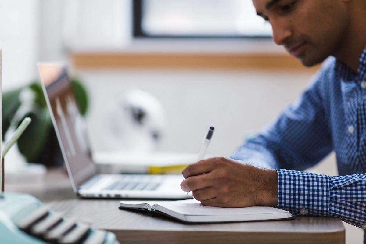 an entrepreneur sitting by his desk correcting his ad copy on a notepad while entering the text copy on his laptop