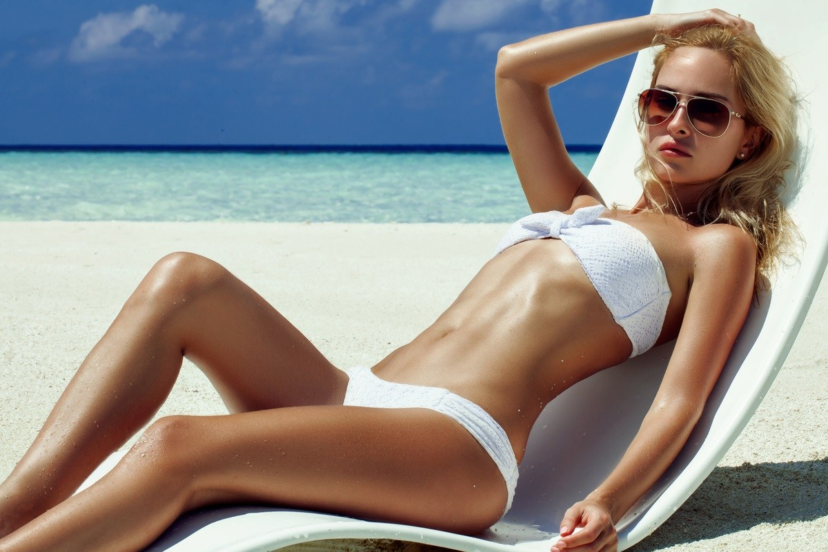 beautiful girl wearing sunglasses in white swimsuit resting on a canopy beach chair by the ocean