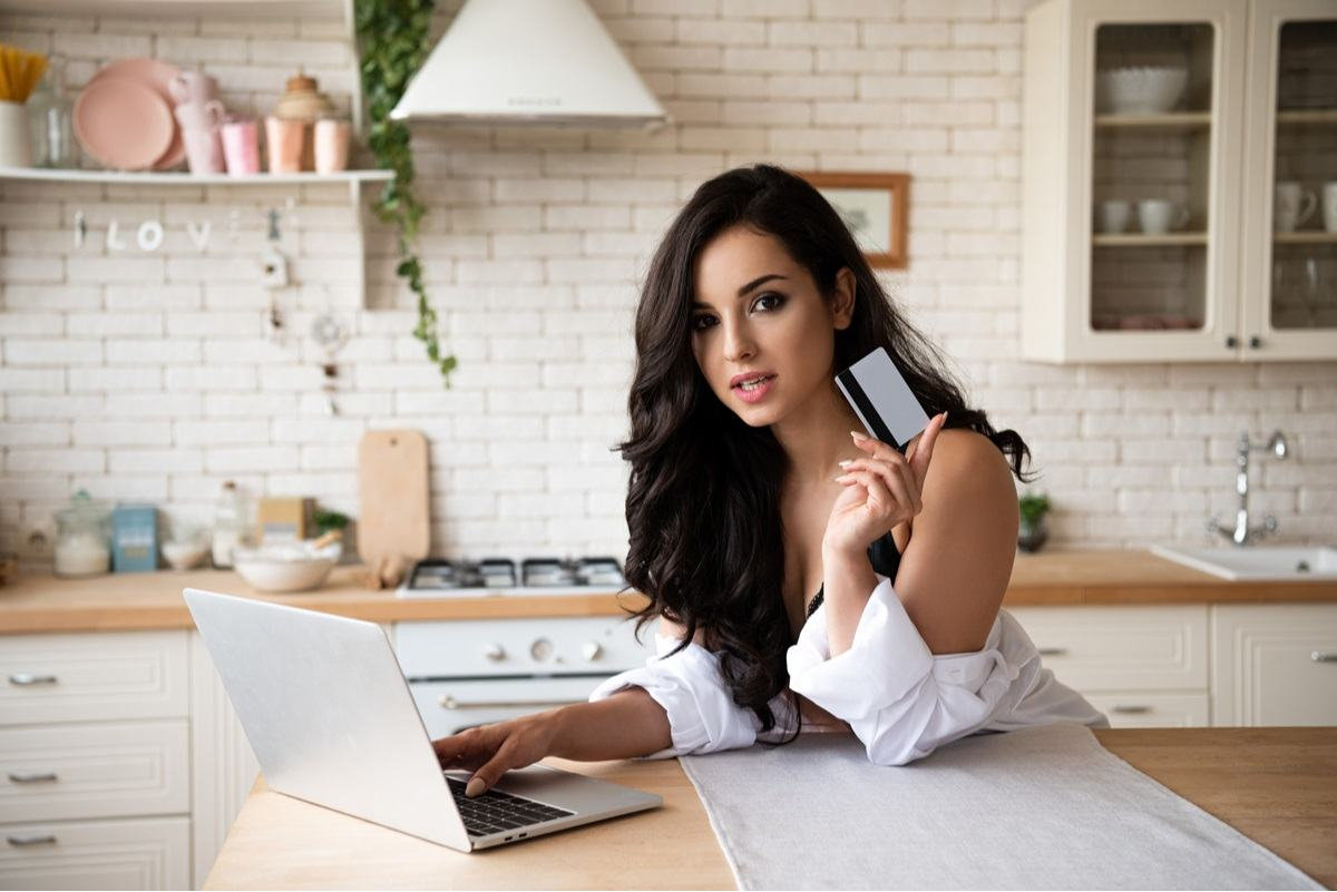 beautiful girl sitting in front of her laptop computer holding a credit card to place an order online