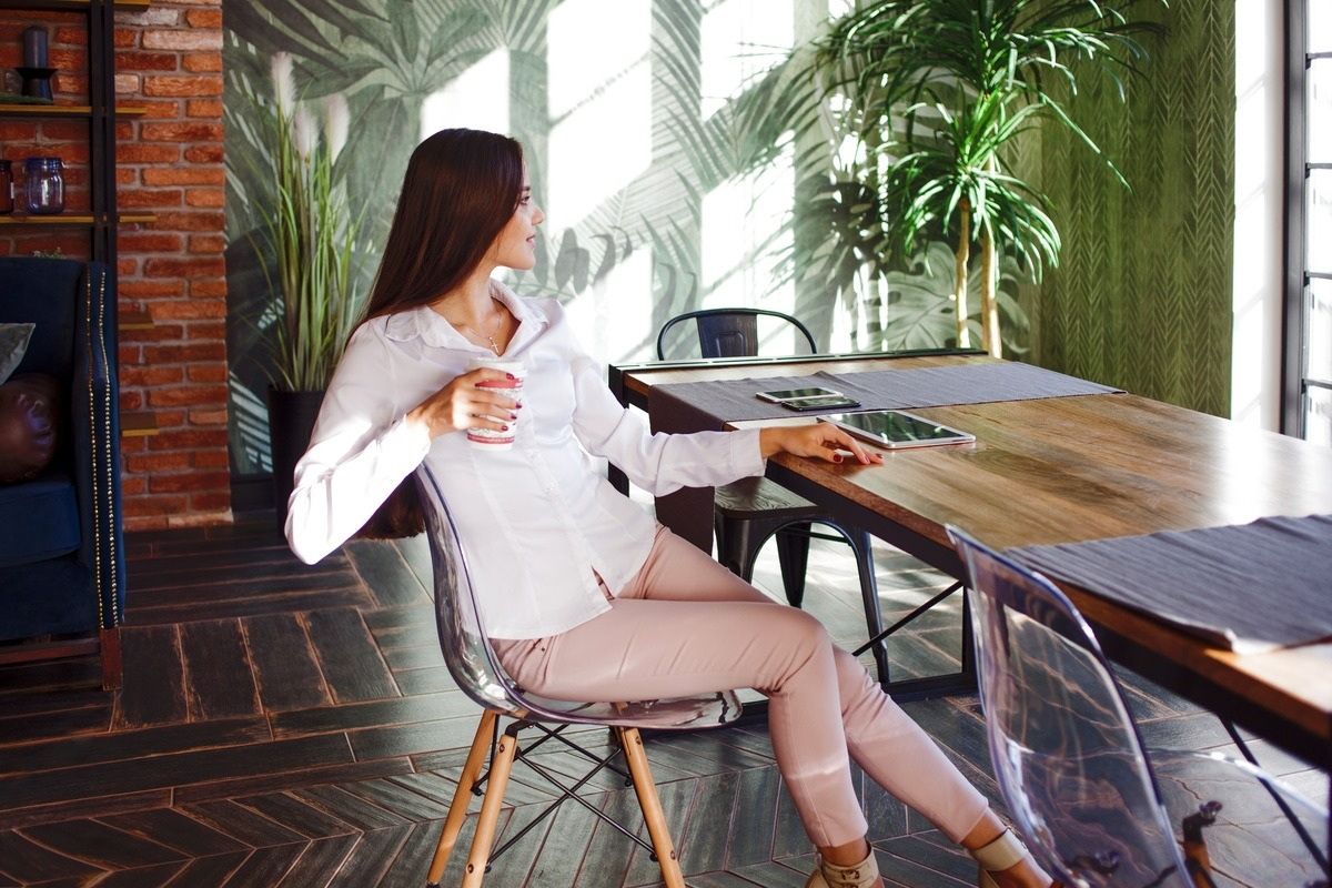 successful business woman relaxing in her mansion with her tablet and smart phone on her desk