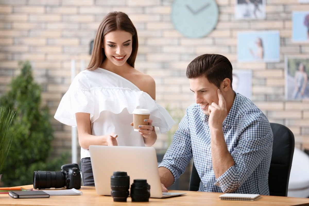 professional model photographer displaying photo shots on his laptop to a female model client