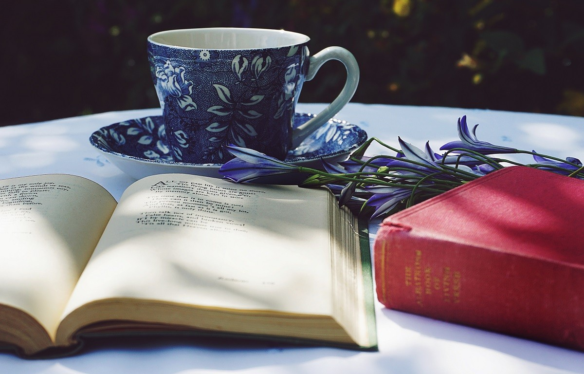 open book next to a coffee cup and some flowers on a small round table