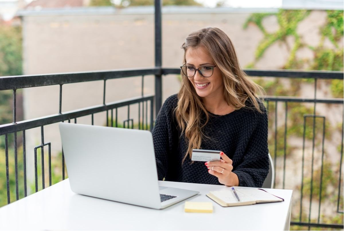beautiful woman sitting outdoor in front of her laptop using her credit card to order online